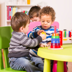 Toddlers helping and sharing in the playroom